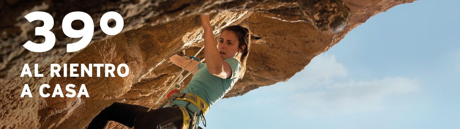 Donna che sta scalando in arrampicata una parete da roccia